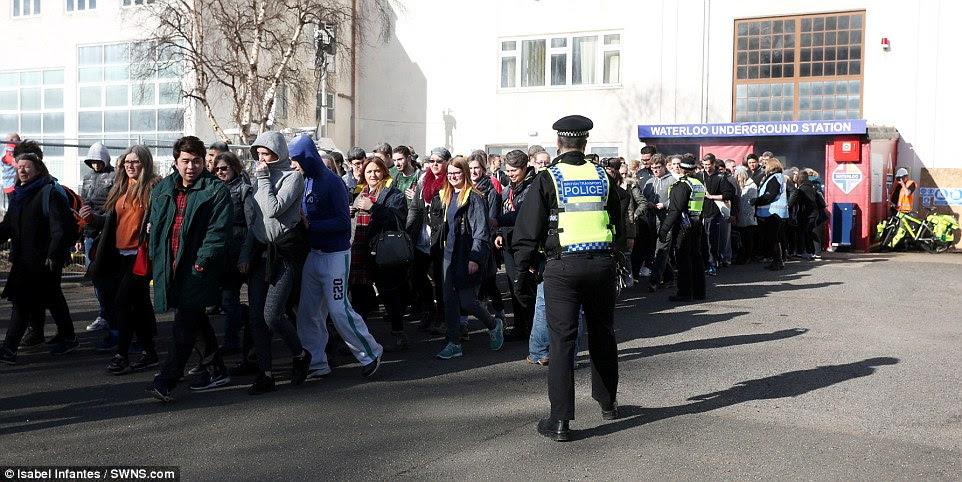 Κατευθύνεται προς την ασφάλεια: Εκατοντάδες φορείς που προσποιείται ότι είναι οι επιβάτες στο σταθμό φαίνονται ήρεμα αφήνοντας τη σκηνή