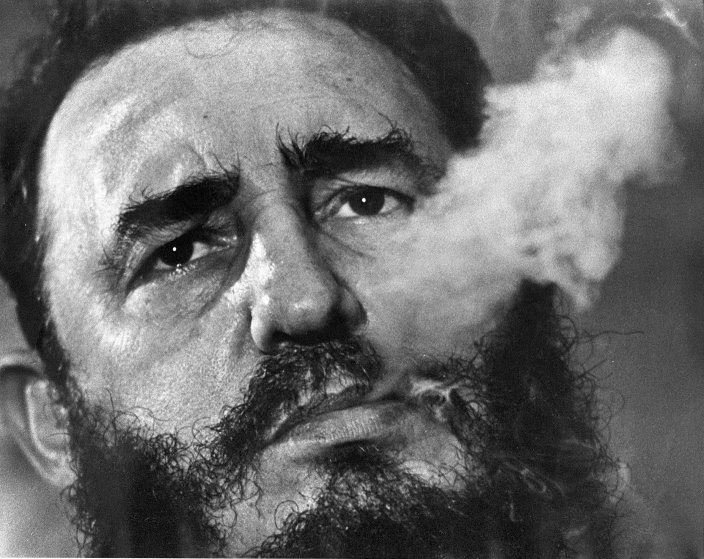 Fidel Castro exhales cigar smoke during an interview at his presidential palace in Havana, March 1985. Charles TasnadiÑAP