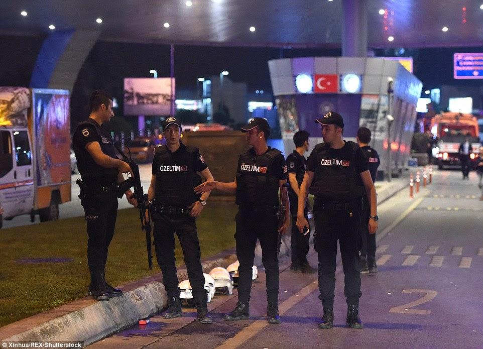 Policiais armados ficar de guarda do lado de fora do aeroporto depois que os passageiros, funcionários e equipe companhia aérea foram evacuados após o ataque devastador