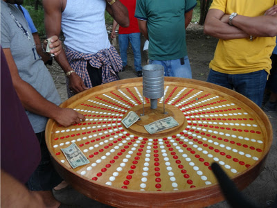 <p>Men gamble on a roulette table under the cover of some trees at Ferry Point Park.</p>