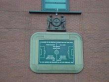 Một bia đá khắc hình ảnh của một sân bóng đá và một số tên cầu thủ. Nó được bao quanh bởi một đường viền đá trong hình dạng của một sân vận động bóng đá. Phía trên bảng là một tấm gỗ khắc hai người đàn ông cầm một vòng hoa lớn.