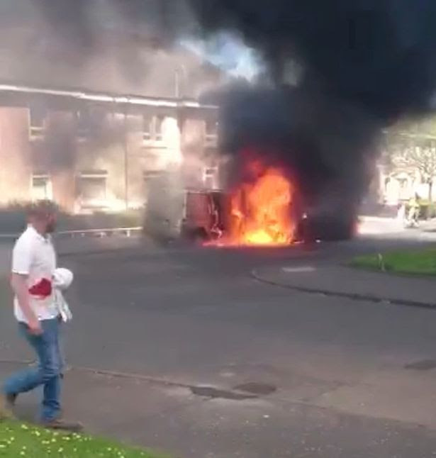 Man soaked in blood walks past burning vans during the incident