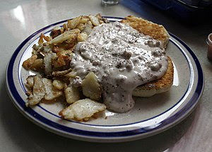 A serving of biscuits and gravy, accompanied b...