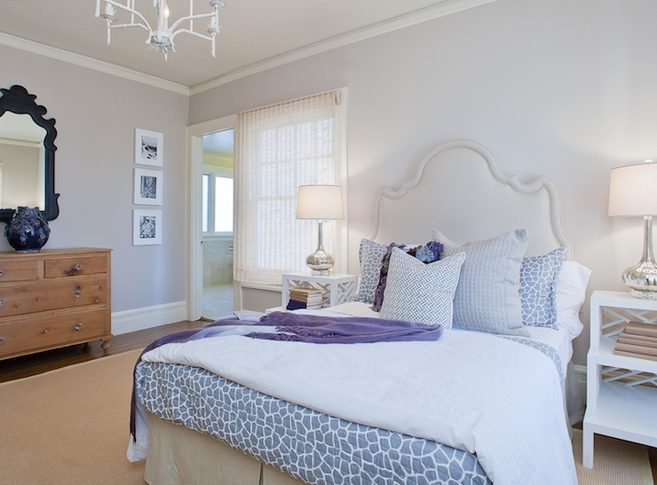 Lilac bedroom with bound sisal rug, white tiered step tables, gray giraffe print