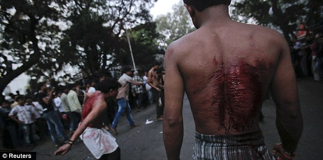 A scarred Shiite Muslim watches another mourner flagellate himself in Mumbai