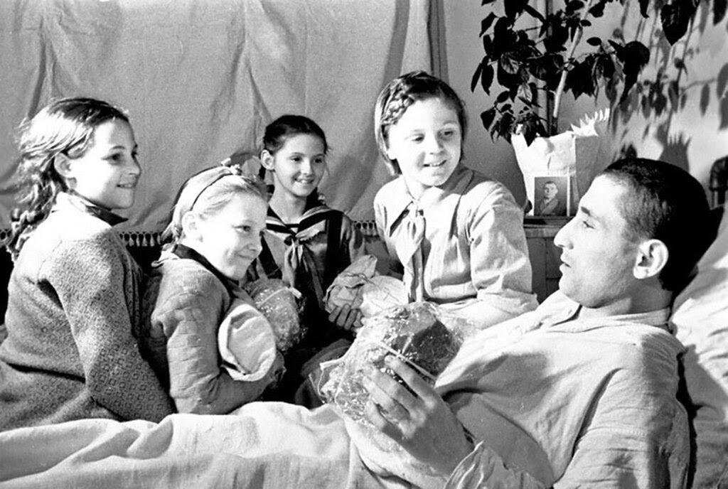 Группа пионеров передает подарки раненому бойцу в  госпитале. 1942 г.