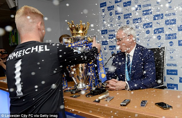Kasper Schmeichel places the Premier League trophy in front of Ranieri after helping his team to a 3-1 win