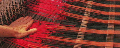 Working the knots through the heddle eyes.