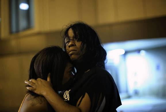 Rochetta Tyler, right,  aunt of three year-old Deonta' Howard, comforts his grandmother Semehca Nunn outside Mt. Sinai Hospital. Deonta' was among 13 people who were shot at Cornell Square Park in the Back of the Yards neighborhood on Thursday.