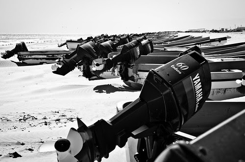 Dozens of boats with two strokes engines on the beach in Oman by Nicola Zingarelli