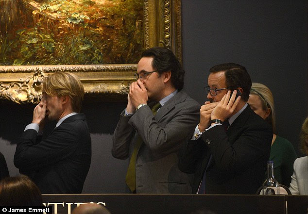 Keeping it quiet: Bidders on phones try to stay discreet. The painting went to an anonymous bidder after taking two minutes to reach its final price