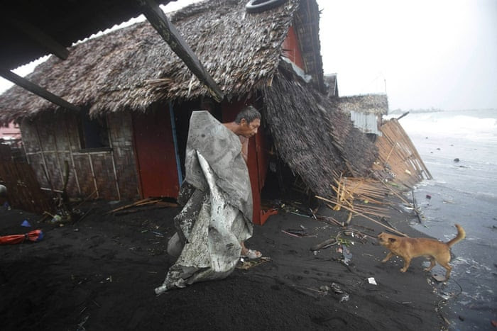 """A Filipino man carries a plastic sheet from his house after strong waves caused by typhoon Hagupit battered a coastal village in Legazpi. Residents began trickling back to their homes when local authorities reported the typhoon had passed. Nearly 900,000 people had moved out of their homes into shelters. <a href=""""http://www.theguardian.com/world/gallery/2014/dec/07/typhoon-hagupit-in-pictures"""">View more images from the typhoon here</a>"""
