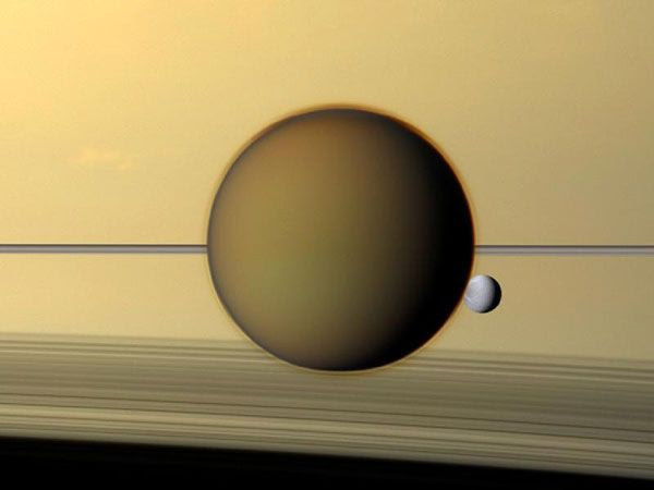 Saturn's third-largest moon Dione can be seen through the haze of its largest moon, Titan, in this natural-color view of the two posing before the planet and its rings from the Cassini spacecraft, on May 21, 2011.