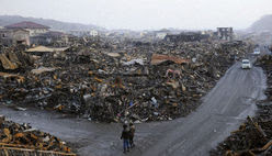 Quake aftermath in Kesennuma: People stand beside piles of debris in the quake-hit city of Kesennuma in Miyagi Prefecture, northeastern Japan, on March 16, 2011. The area was devastated by a massive earthquake and tsunami on March 11. (Kyodo, used w/o permission)