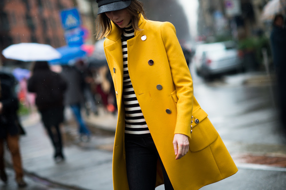 Anya Ziourova is wearing black jeans and a black and white striped turtleneck sweater. Quite basic, yes. But then she added this happy yellow coat and that definitely takes her outfit to the next level.  GET THE LOOK: