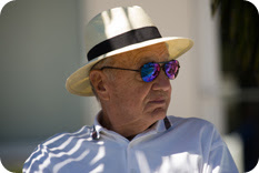 Older man wearing hat and sunglasses sitting in shade