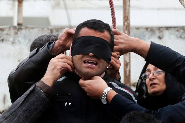 This picture provided by ISNA, a semi-official news agency, taken on Tuesday, April 15, 2014 shows Maryam Hosseinzadeh, right, and her husband Abdolghani, left, removing the noose from the neck of blindfolded Bilal who was convicted of murdering their son Abdollah in the northern city of Nour, Iran. Bilal who was convicted of killing Abdollah Hosseinzadeh, was pardoned by the victim's family moments before being executed.