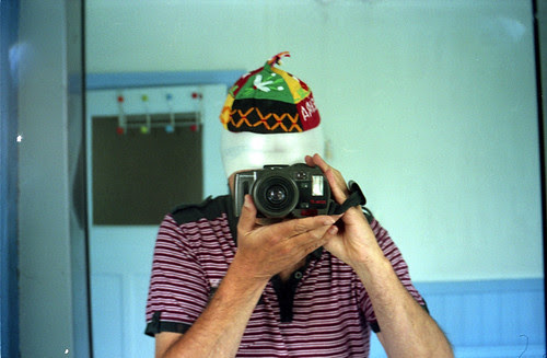 reflected self-portrait with Olympus AZ-330 Superzoom camera and Maltese hat by pho-Tony