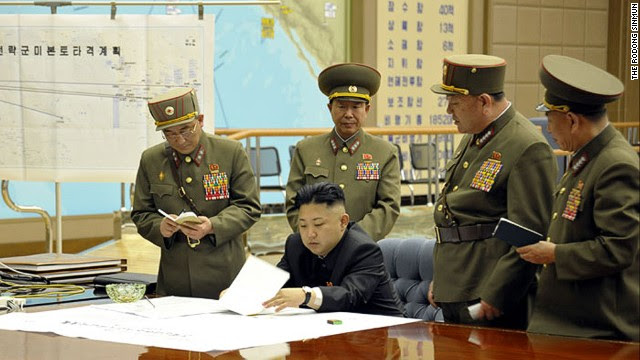 "Kim Jong Un is briefed by his generals in this undated photo. On the wall is a map titled ""Plan for the strategic forces to target mainland U.S."""