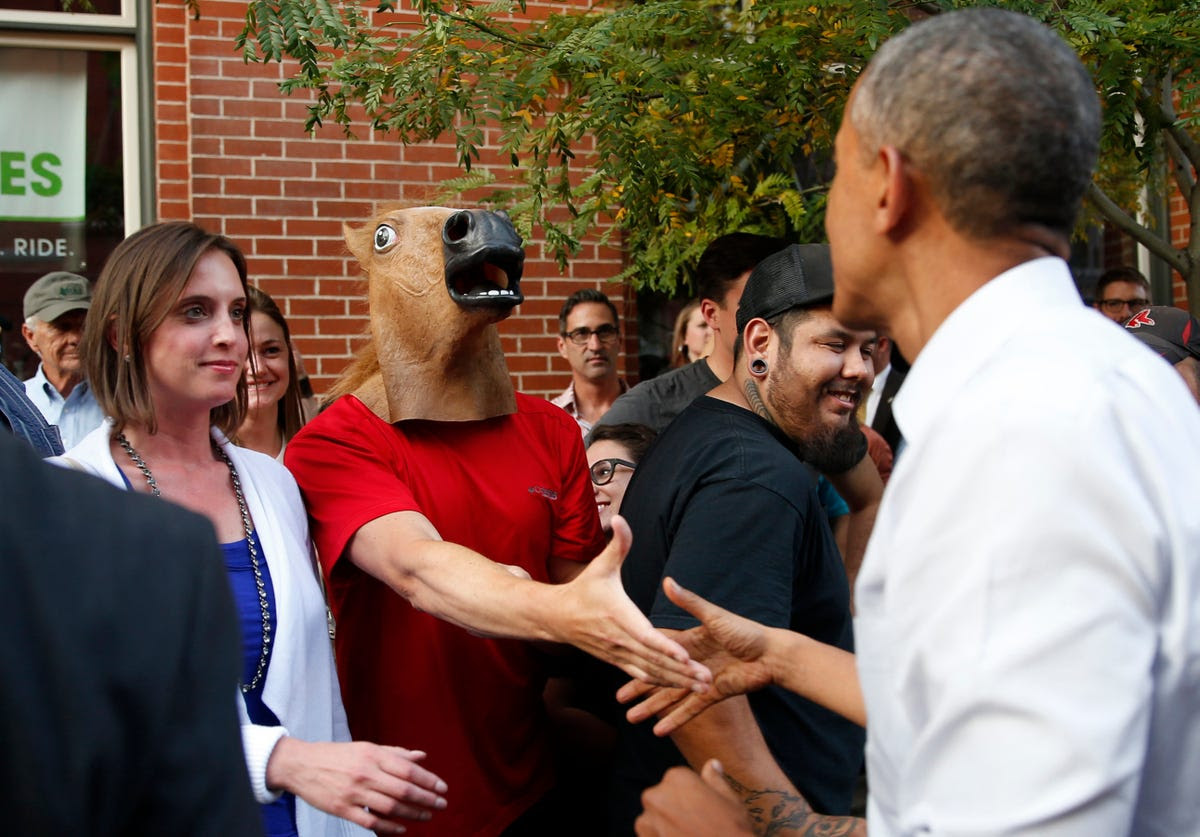 US President Barack Obama greets a man wearing a horse mask during a walkabout in Denver on July 8.