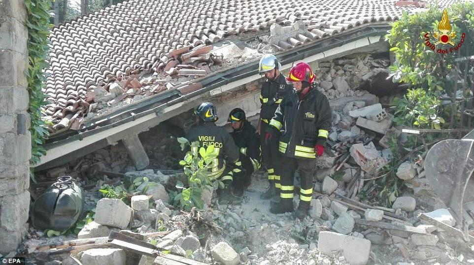 Sinais de vida: o corpo de bombeiros italianos são vistos trabalhando em uma casa desabou e danificou em Amatrice que parece ter sido reduzido a um telhado