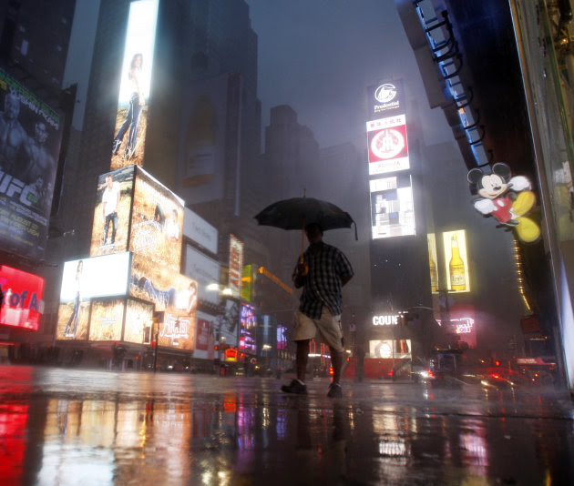 A man walks in Times Square as  Hurricane Irene arrives in New York, on Sunday, Aug. 28, 2011. (AP Photo/Mike Groll)