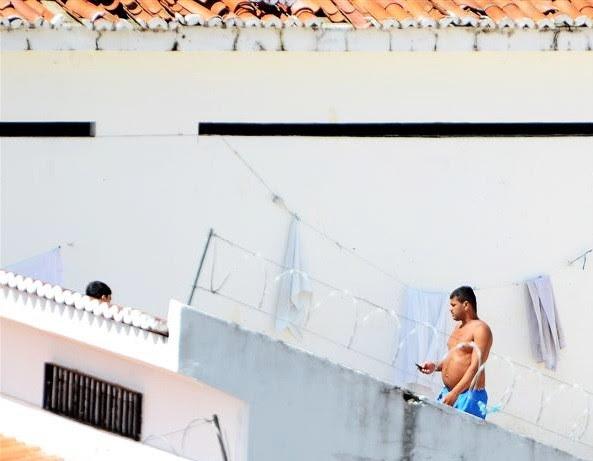 Segundo a direção de Alcaçuz, fotos que mostram preso fazendo uso de um aparelho celular foram feitas do alto de uma das guaritas da unidade (Foto: Divulgação/Tribuna do Norte)