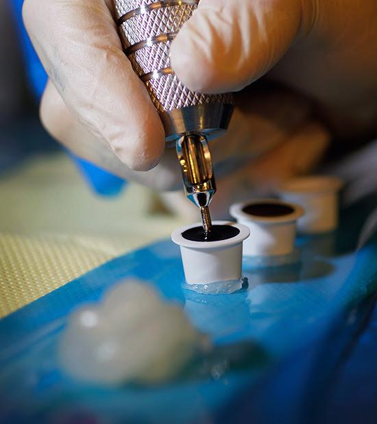 Tatuador William Coy carrega a agulha com tinta preta em seu estúdio em Miami nos EUA