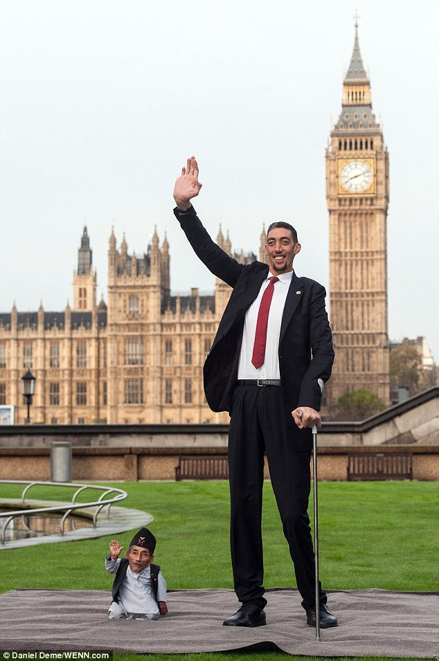 (Very) high five: Mr Dangi, who measures just 22.5 ins, and 8ft 1in tall Mr Kosen, meet in London today