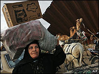 A woman carries goods from Egypt across the border with Gaza