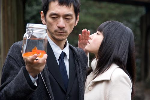 The woman (Rukino Fujisaki) whispers something to the man (Takao Kawaguchi)