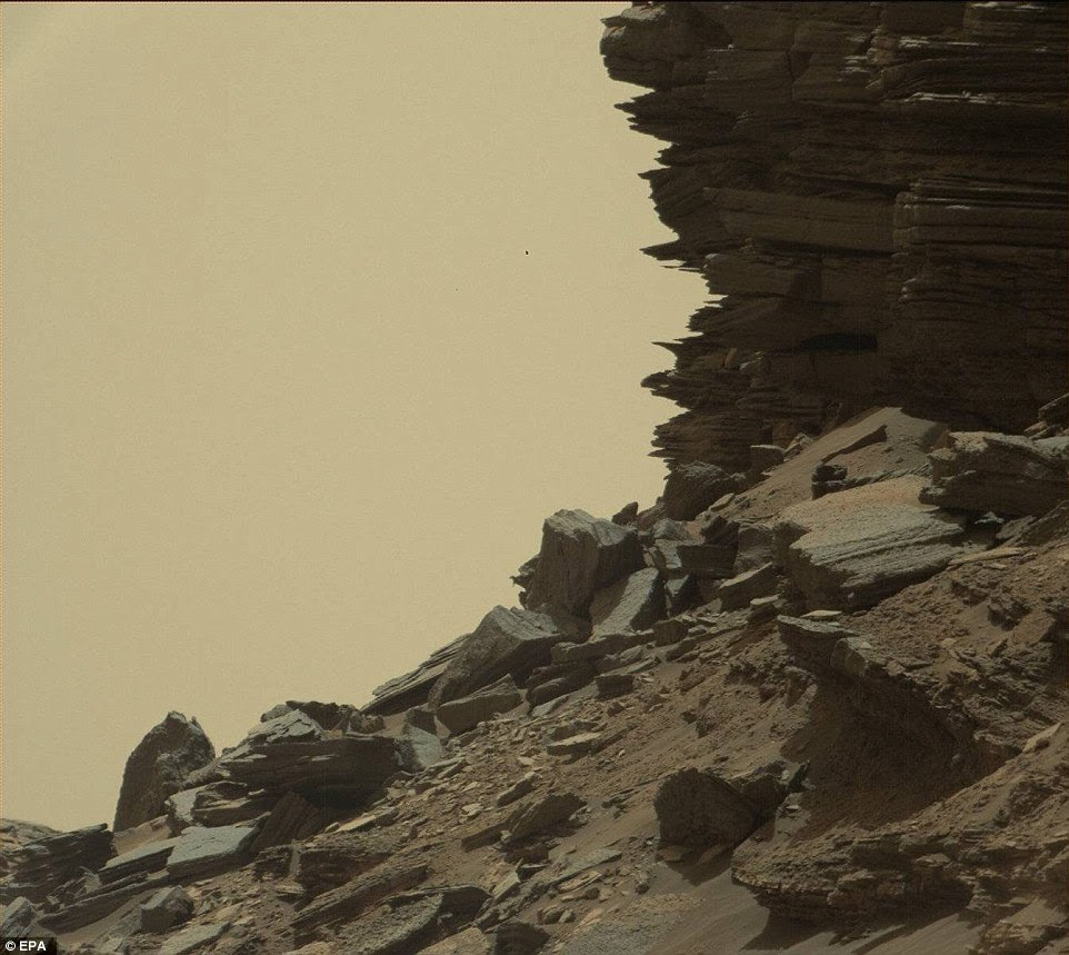 NASA says the Martian buttes and mesas rising above the surface are eroded remnants of ancient sandstone that originated when winds deposited sand after lower Mount Sharp had formed.