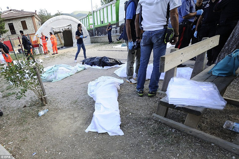 Recovered bodies lay covered on the ground in a child's play area in the town of Pescara del Tronto