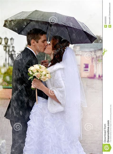 Beautiful wedding couple kissing in the rain. Bride and groom