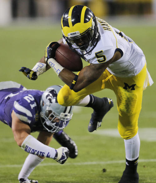 Michigan RB Justice Hayes rushes past Kansas State's Jonathan Truman in the Wildcats' 31-17 win in the Buffalo Wild Wings Bowl Saturday in Tempe. (Credit: AP)