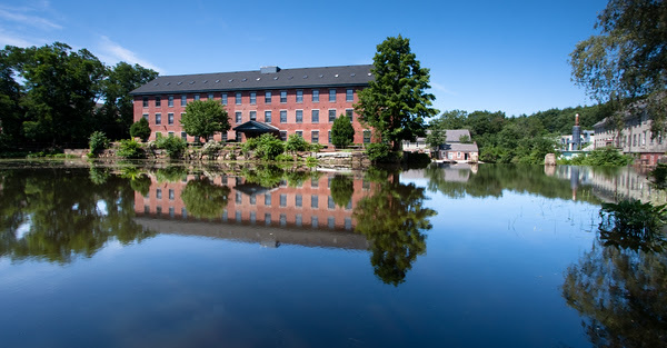 mill buildings reflecting in smooth water