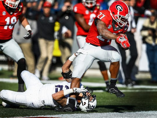 Georgia running back Nick Chubb (27) runs over TCU defender Niko Small for a touchdown in the fourth quarter of the Liberty Bowl NCAA college football game, Friday, Dec. 30, 2016, in Memphis, Tenn. (Mark Weber/The Commercial Appeal via AP)