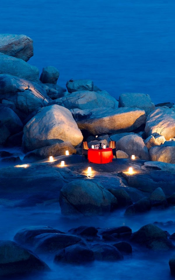 lantern and candle lit dinner on a rocky shore