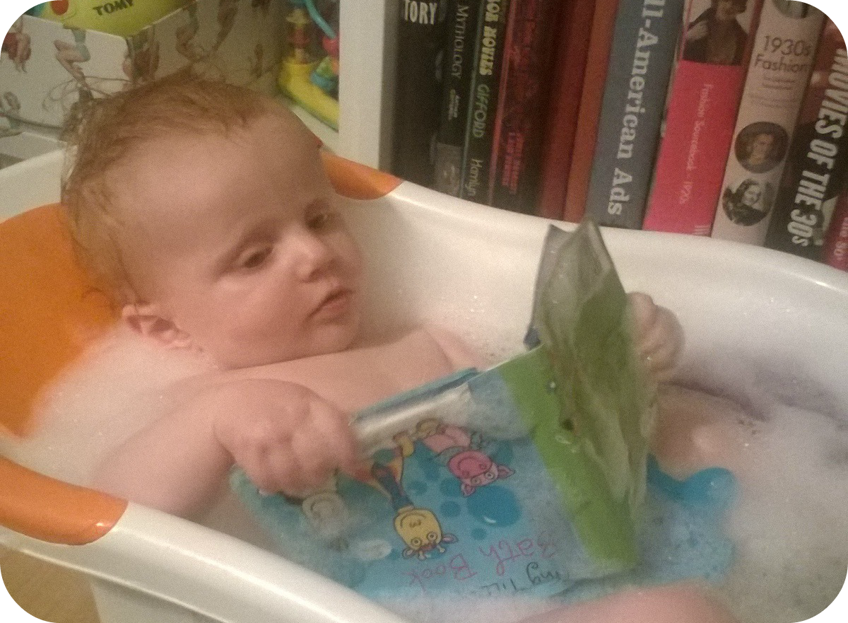 Marianna in the bath with a baby book