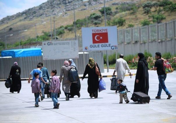 599526_des-refugies-syriens-en-turquie-rentrent-dans-leur-pays-apres-un-attentat-dans-la-province-de-hatay-le-14-mai-2013
