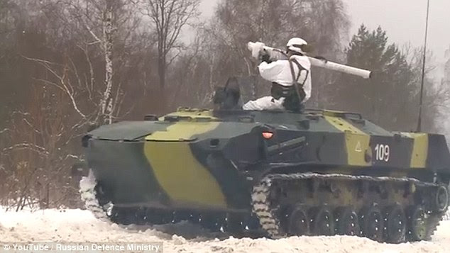 A Russian soldier in snow-camouflage prepares to fire the missile from a tank