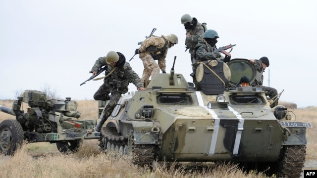 Ukrainian soldiers clamber aboard an armoured vehicle near Mariupol. (file photo)