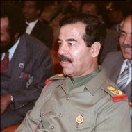 """Iraqi President Saddam Hussein 10 November 1987 in Amman during a session of the emergency Arab summit. Saddam took the number two job under president Ahamd Hassan al-Bakr, began purging the army of non-Baathist officers, ridding the political scene of Kurds and communists. When Bakr stepped down, officially for health reasons, the stage was set for Saddam, who became president on 16 July 1979. Fearing the impact of Tehran's Islamic revolution on Iraq's majority Shiite Moslem population, Saddam launched a war against Iran in 1980 to defend """"the eastern flank of the Arab nation from the Persian. But he only managed to obtain a cease-fire in 1988. On 02 August 1990, Saddam directed his army against Kuwait. In February 1991 a multinational coalition led by the United States chased Iraqi troops out of he emirate.  (Photo credit should read MONA SHARAF/AFP/Getty Images)"""