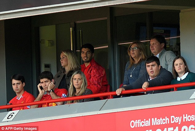 Watching on: Luis Suarez watches the action at Anfield