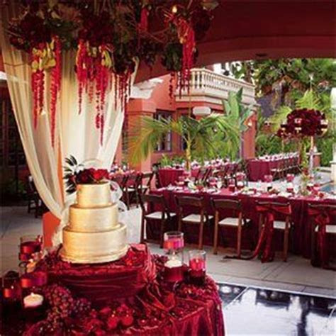 Gold sheen on cake, garnet wrapped cake table.   Red