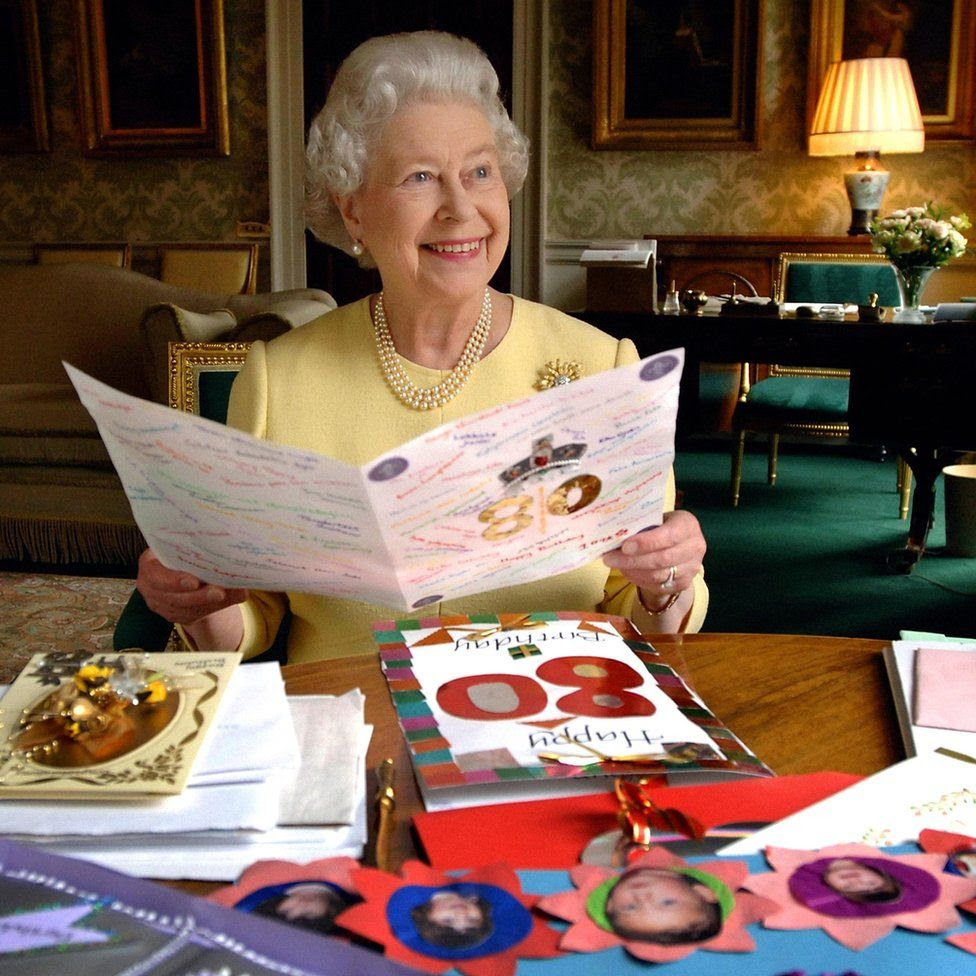 Queen Elizabeth II sitting in the Regency Room at Buckingham Palace in London looking at some of the cards which were sent to her for her 80th birthday
