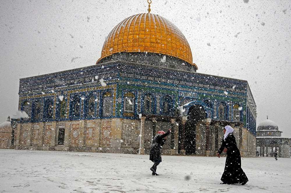 Two Palestinian women play with snow outside Al-Aqsa Mosque in Jerusalem. (AP Photo/Mahmoud Illean)