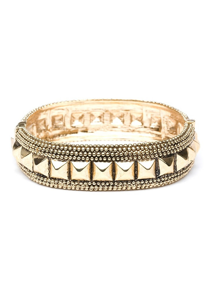 The Midas touch gets a shot of punk glamour in this cool bangle. Cast in gold, it works an exotic handcrafted vibe—just check out that intricate caviar beading—while the spiky pyramid studs exude CBGB chic.