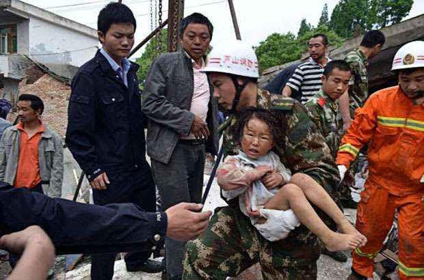 Bombeiro carrega criança resgatada após tremor (CHINA OUT AFP PHOTO )