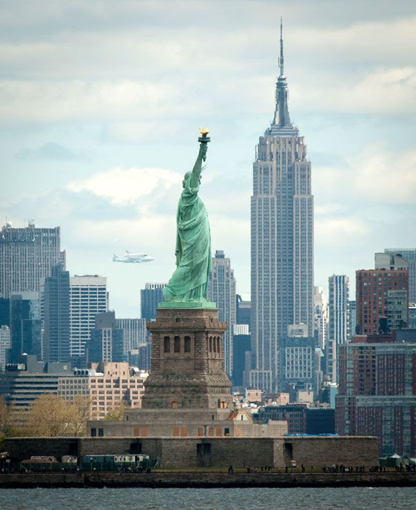 With the Statue of Liberty and Empire State Building in the foreground, the shuttle Enterprise and NASA 905 fly over New York City on April 27, 2012.